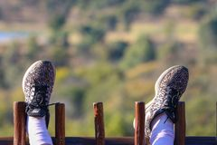 Person Wearing Black and Grey Nike Shoes Resting Feet on Wooden Fence royalty free stock photos