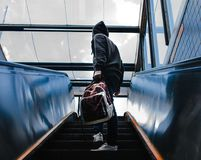 Person Wearing Black Hooded Jacket Standing on Escalator While Holding Backpack Stock Photos