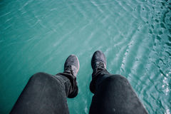 Person Wearing Black Jeans and Black Sneakers Beside Body of Water Stock Images