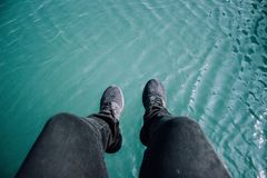Person Wearing Black Jeans and Black Sneakers Beside Body of Water Royalty Free Stock Photography