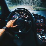 Person Wearing Black Sports Band Apple Watch Driving Audi Car during Rainy Day Stock Image
