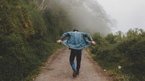 Person Wearing Blue Denim Jacket While Walking on Foggy Road Royalty Free Stock Photo