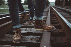 Person Wearing Blue Denim Jeans and Brown Leather Shoes Standing in Railway during Daylight Stock Image