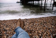 Person Wearing Blue Denim Pants and Brown Boots Sitting on Brown and Black Stone in Front of Body of Water Royalty Free Stock Image