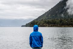 Person Wearing Blue Hoodie Near Body of Water Royalty Free Stock Photography
