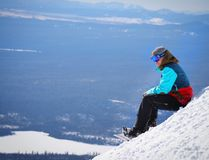Person Wearing Blue and Red Winter Jacket Sitting on White Snow Mountain Royalty Free Stock Image