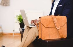 Person Wearing Blue Suit Beside Crossbody Bag and Using Macbook royalty free stock photo