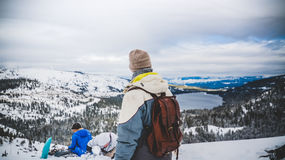 Person Wearing a Blue and White Jacket and Brown Backpack Standing on Mountains Royalty Free Stock Image