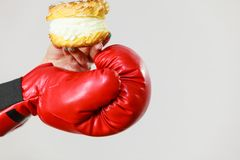 Person wearing boxing gloves holding cream cake. Cupcake. Beating calories and fighting for weight loss concept Royalty Free Stock Images