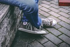 Person Wearing Brown Converse All-star High-top Sneakers and Blue Denim Jeans While Sitting on Bench Stock Photography