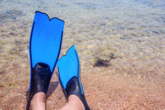 Person wearing fins lying at the edge of the sea Stock Photo