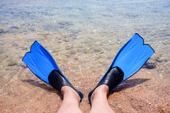 Person wearing fins lying at the edge of the sea Royalty Free Stock Images