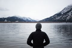 Person Wearing Gray Bonnet and Black Jacket on Lake Stock Image