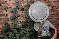 Person Wearing Gray Crew-neck T-shirt holding a tray on the face next to a brick wall Royalty Free Stock Image