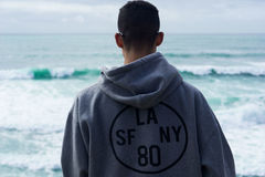Person Wearing Gray Hoodie With La Sf Ny 80 Print Near Body of Water during Daytime Royalty Free Stock Images