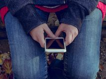 Person Wearing Gray Sweater and Blue Jeans Holding a White Smartphone Royalty Free Stock Photography