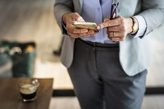 Person Wearing Grey Suit Jacket And Black Bottoms Standing Near Brown Wooden Table Holding Smartphone royalty free stock photography