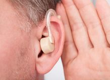 Person wearing hearing aid. Close-up Of A Person Wearing Hearing Aid royalty free stock photos