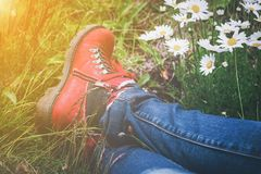 Person wearing hiking boots lying in a meadow. With white spring daisies and golden glow from the sun in a close up view of the feet Royalty Free Stock Photo