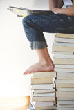 Person Wearing Jeans Sitting on Books Stock Image