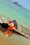 Person wearing life vest. Lie down at beach Stock Images