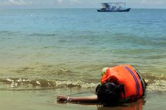 Person wearing life vest. Lie down at beach stock image