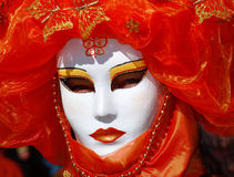 Person Wearing Mask. Person in Venetian Mask and Orange-colored costume during Carnival Stock Images