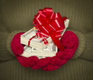 Person Wearing Mittens Holding Stacks of Money with Red Ribbon Royalty Free Stock Photo