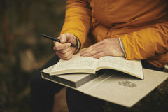Person Wearing Orange Holding Pen and Book Royalty Free Stock Images