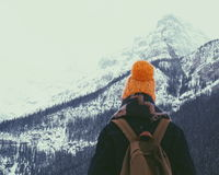 Person Wearing Orange Knit Hat Overlooking Snowy Mountain Royalty Free Stock Photography