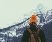 Person Wearing Orange Knit Hat Overlooking Snowy Mountain Royalty Free Stock Photo