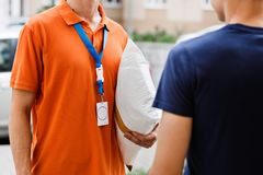 A person wearing an orange T-shirt and a name tag is delivering a parcel to a client. Friendly worker, high quality stock image