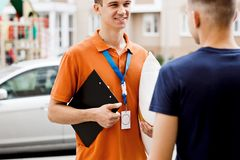 A person wearing an orange T-shirt and a name tag and holding a clipboard is delivering a parcel to a client. Friendly stock images
