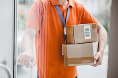 A person wearing an orange T-shirt and a name tag is standing behind the glass door and holding a door handle and royalty free stock image