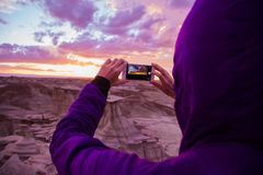 Person Wearing Purple Hoodie Jacket Holding Iphone 6 during Golden Hour Royalty Free Stock Photos