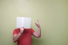 Person Wearing Red Cap Sleeve Shirt Holding and Covering Face by Book Stock Photo