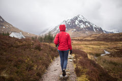 Person Wearing Red Hoodie Walking Between Green Grass Towards Rocky Mountain during Day Time Royalty Free Stock Photo
