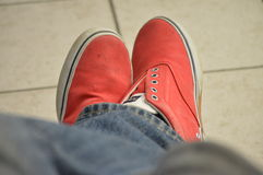Person wearing red shoes and jeans crossed legs Stock Images