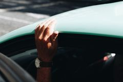 Person Wearing Round White Analog Watch Black Strap Holding on Vehicle Roof Royalty Free Stock Images