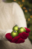 Person Wearing Seasonal Red Mittens que guarda o Natal verde Ornam imagens de stock royalty free