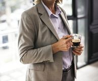 Person Wearing Suit Jacket Holding Glass Mug stock photography