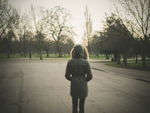 Person wearing warm coat standing in park at sunset Stock Photos