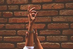 Person Wearing Watch and Rings Raising Left Hand Near Brick Wall royalty free stock image