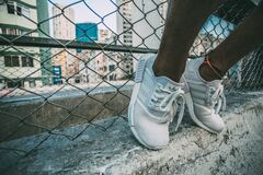 Person Wearing White Adidas Low Top Shoe Near Gray Cyclone Fence Royalty Free Stock Image