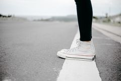 Person Wearing White High-top Lace-up Sneakers Standing on White Line stock photo