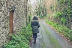 Person wearing winter coat walking in countryside Royalty Free Stock Image