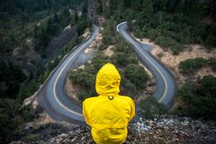 Person Wearing Yellow Hoodie Jacket Sitting Near a Cliff Royalty Free Stock Photography