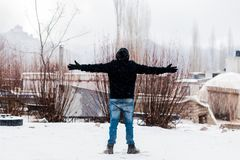Person Wears Black Jacket and Blue Denim Jeans Standing on Snow Covered Field Stock Photos