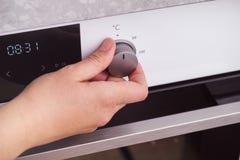 Person, welche die Temperatur in Celsius auf dem Ofen einstellt lizenzfreie stockfotos
