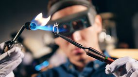 Person welds metal ring while working at a jewellery workshop. 4K stock footage